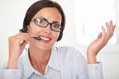 stock photo of spectacles  - Pretty female employee with spectacles talking on headphones while smiling and looking at you - JPG