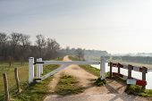 picture of dike  - White gate on a Dutch dike for closing the road for cars - JPG