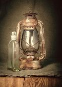 picture of kerosene lamp  - old rusty kerosene lamp and a bottle of kerosene on the wooden floor on the burlap background - JPG