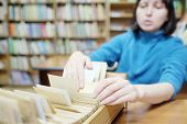 picture of librarian  - Librarian woman searches something in card catalog - JPG