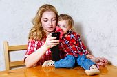 stock photo of feeding  - Mother give drink her baby girl by feeding bottle - JPG