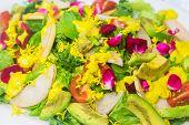 stock photo of hawaiian flower  - Hawaiian salad made with kale tomatoes avocado edible flowers and mango dressing - JPG