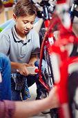 foto of lubricant  - Little boy lubricating bike wheel chain - JPG