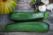 image of basil leaves  - Fresh green zuchinni squash with basil leaves and garlic on wooden board top view - JPG