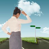 stock photo of scratching head  - Businesswoman scratching her head against road leading out to the horizon - JPG