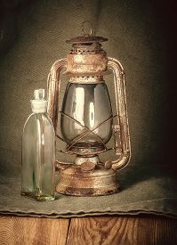stock photo of kerosene lamp  - old rusty kerosene lamp and a bottle of kerosene on the wooden floor on the burlap background - JPG
