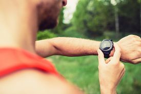 image of check  - Runner on mountain forest trail checking looking at sportwatch smart watch cross country runner checking performance GPS position or heart rate pulse - JPG