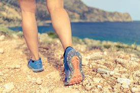 picture of motivation  - Walking running hiking or exercising sports shoe and legs on rocky hiking trail in mountains motivation inspiration concept outdoors achievement fitness adventure and exercising in wild nature seaside - JPG