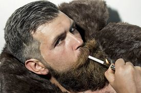 picture of long beard  - Portrait of sexual unshaven man with long beard and moustache in brown fur coat with collar lying in white bath tub and smoking cigarette horizontal picture - JPG