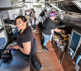 stock photo of food truck  - Happy cashier with payment on busy food truck - JPG