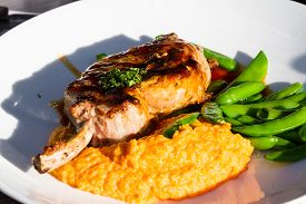 image of sweet pea  - french cut pork chop served with a sweet potato puree and green peas on a white plate - JPG