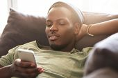 Indoor Shot Of Smiling Black Young Man Surfing Internet On Mobile Phone, Messaging Friends Online An poster