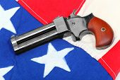 picture of derringer pistol  - Double derringer pistol on a american flag - JPG