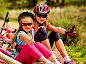 Mother and daughter on bicycle. Bikes cycling family. Happy mother and daughter are sitting on green poster