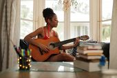 Mixed Race Girl Singing And Playing Classic Guitar At Home poster