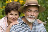 image of elderly couple  - Happy elderly couple embracing in the garden - JPG