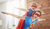 Mother and her child playing together. Girl and mom in Superhero costume. Mum and kid having fun, sm poster