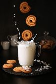 Falling Cookies To Glass Of Milk With Splash On Black Background poster