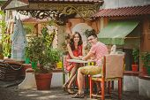 Young Beautiful Happy Loving Couple Sitting At Street Open-air Cafe Looking At Camera. Beginning Of poster