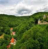 View on green hills and medieval remains of castle in Karlstejn, Czech Republic.