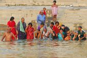 hindu family of men and women bathing in the ganges river