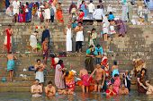 hindu men and women, bathing in holy ganges in varanasi