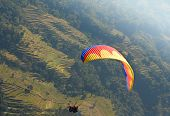 paragliding in nepal above green rice terraces