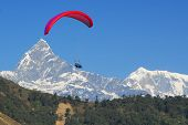 paragliding in nepal with view on fishtail mountain of the himalaya (photo taken during paraglide)