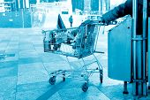 Homeless man with shopping cart searching the trash for food in blue tone