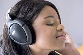 Attractive Young Black Woman Listening To Music On Headphonesat