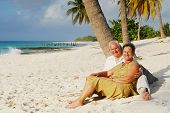 Happy senior couple sitting on the beach embracing each other, enjoying retirement on tropical desti