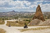 picture of riding-crop  - Landscape of dirt riding in Cappadocia on the outskirts of Goreme with Uchisar on the hill backdrop horizontal crop margins with negative space - JPG