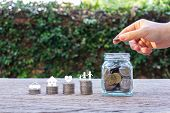 Savings Money For Family Life Concepts. Hand Holding Coin On A Full Money In Glass Jar And Family Me poster
