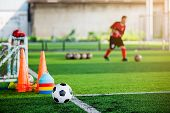 Football And Soccer Training Equipment On Green Artificial Turf With Blurry Of Soccer Players Traini poster