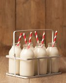 Crate of vintage milk bottles with red and white striped drinking straws in rustic setting