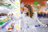 Beautiful young woman shopping for fruits and vegetables in produce department of a grocery store/supermarket (color toned image)