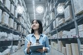 Portrait Of Young Attractive Asian Entrepreneur Woman Looking At Inventory In Warehouse With Smart T poster