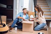 Cheerful Husband Looking At Wife Unpacking Box And Holding Lamp In Hands While Sitting On Floor poster