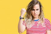 Beautiful young blonde woman over isolated background angry and mad raising fist frustrated and furi poster