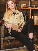 Lady On Dreamy Face In Plaid Clothes Looks Casual. Girl Student Relaxing With Book And Glass Of Mull poster