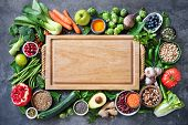 Healthy food selection with fruits, vegetables, seeds, super foods, cereals and the cutting board in poster