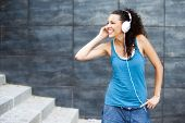 Young happy sportive woman in urban background listening music