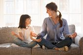 Mindful Mom Teaching Yoga Happy Child Daughter Sitting On Couch poster