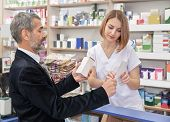 Beautiful Woman Working In Drugstore And Helping, Consulting Clients. Mature Man Showing Prescriptio poster