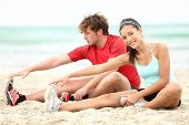 Couple training on beach stretching legs after running. Young man and woman during summer workout. A
