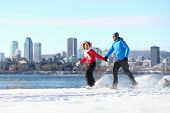 Winter fun couple on snowshoes running with montreal cityscape skyline and river st. Lawrence in bac