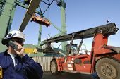 port worker in hardhat, forklift and container crane in the background