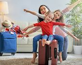 Go on an adventure! Happy family preparing for the journey. Mom and daughters are packing suitcases  poster