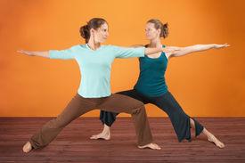 foto of yoga mat  - Two Caucasian women practicing yoga stretch their legs - JPG