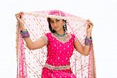 stock photo of bangla  - Beautiful Bangali bride in colorful dress and lifting her veil isolated - JPG